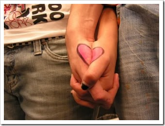 Couple clasping hands. Each wrist has half a heart on it. Joined hands make a whole heart.