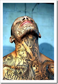 Man's upper body, face and neck covered in tattoos