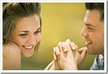 Man and woman facing each other. Man is holding her hands. Woman is looking shy