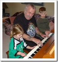 Grandfather playing piano with two grandchildren