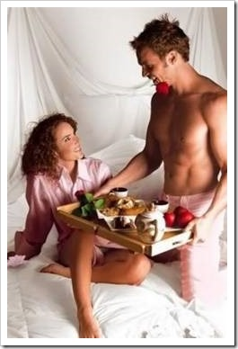 Man serving woman breakfast in bed