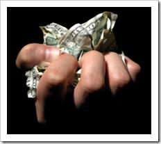 A hand crumpling dollar bills