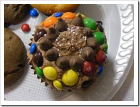 Cupcake decorated with chocolate icing, chocolate chips, skittles and M & M's