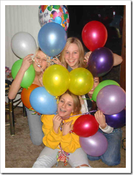 Teenage girls peeping through a bunch of balloons