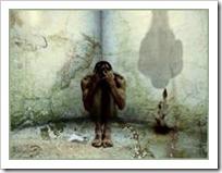 Shamed man crouched in corner