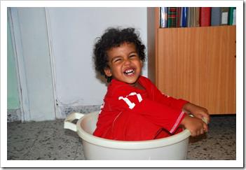 Little boy playing in a tub