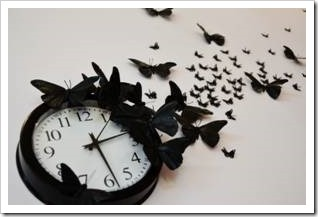 Black clock surrounded by black butterflies
