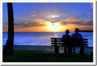 Older couple sitting on a bench watching the sunrise