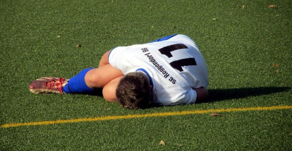 Boy lying on a football field