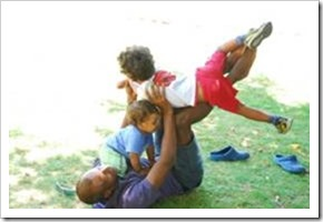 Man playing with two children in the grass