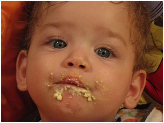 Baby with baby food on his face