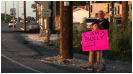 Child with sign I am a bully. Honk if you hate bullies.