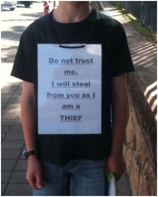 Child wearing a sign around his neck do not trust me I will steal from you as I am a thief