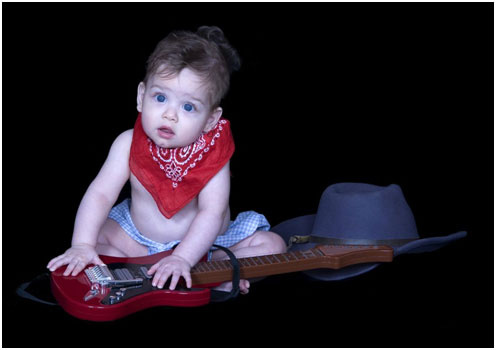 Baby leaning on a guitar