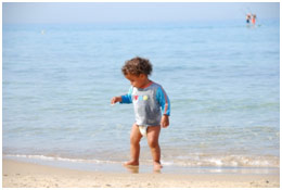 Baby walking down the beach