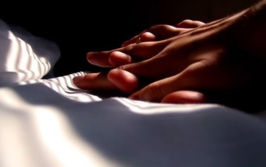 Two hands clasped on a sheet