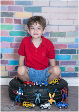 Boy sitting in a car tyre