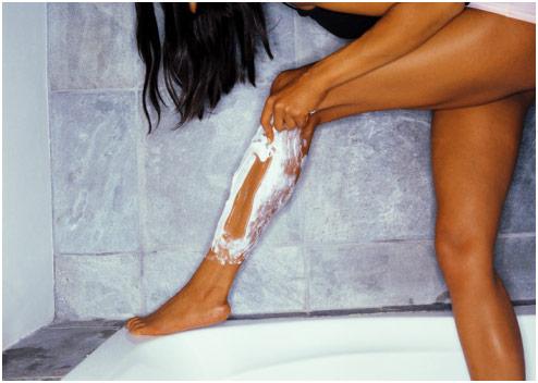A girl shaving her legs in the bathtub