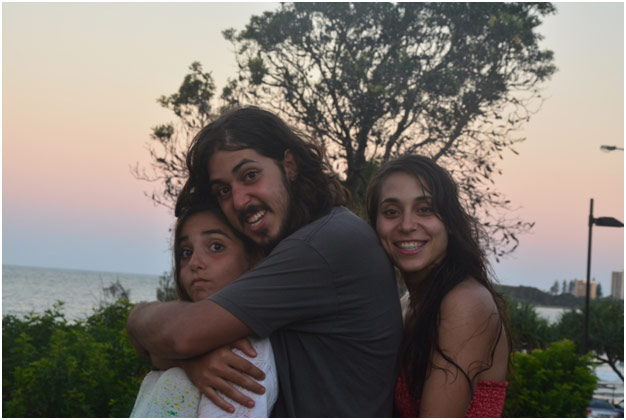 Brother and two sisters hugging in the sunset