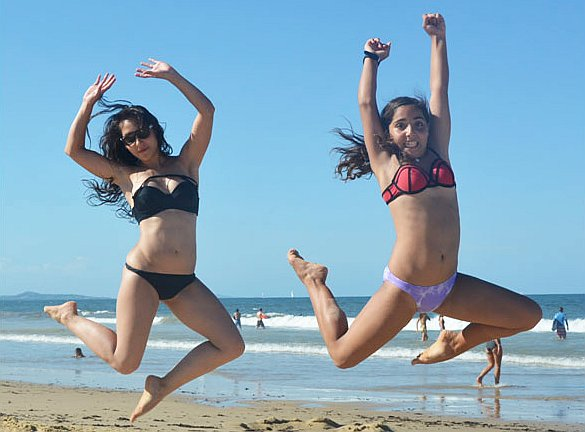 Two sisters jumping on the beach