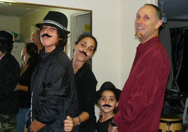Father and kids wearing fake moustaches