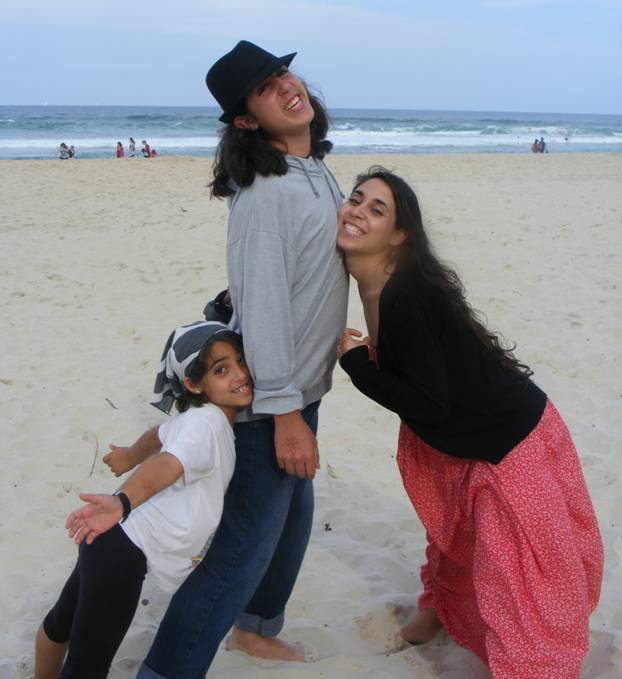 3 siblings clowning around on the beach