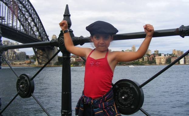 Girl showing her muscles in front of the Sydney Harbour Bridge