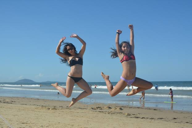 2 girls jumping happily in the air on a beach - they know how to calm anxiety