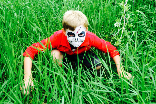 Boy in grass with zombie mask