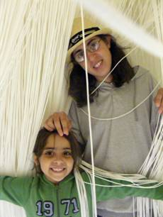 Tsoof and Noff in a museum exhibit with strings hanging from the ceiling