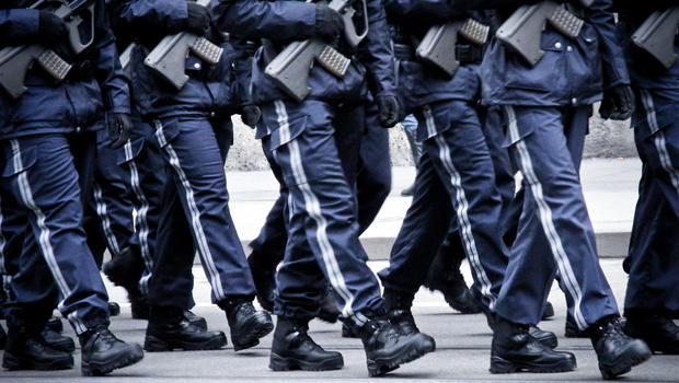 Soldiers marching in blue uniforms holding automatic rifles