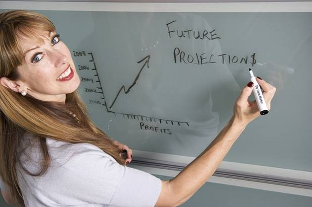 Woman standing next to board showing a graph of profits trending upwards