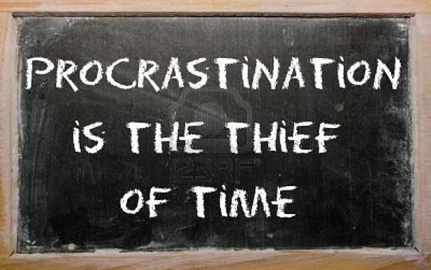 Procrastination is the thief of time written on a blackboard