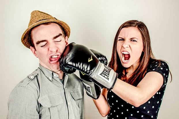 Woman punching man in anger with boxing glove