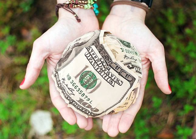 Hands holding a ball of $100 dollar bills