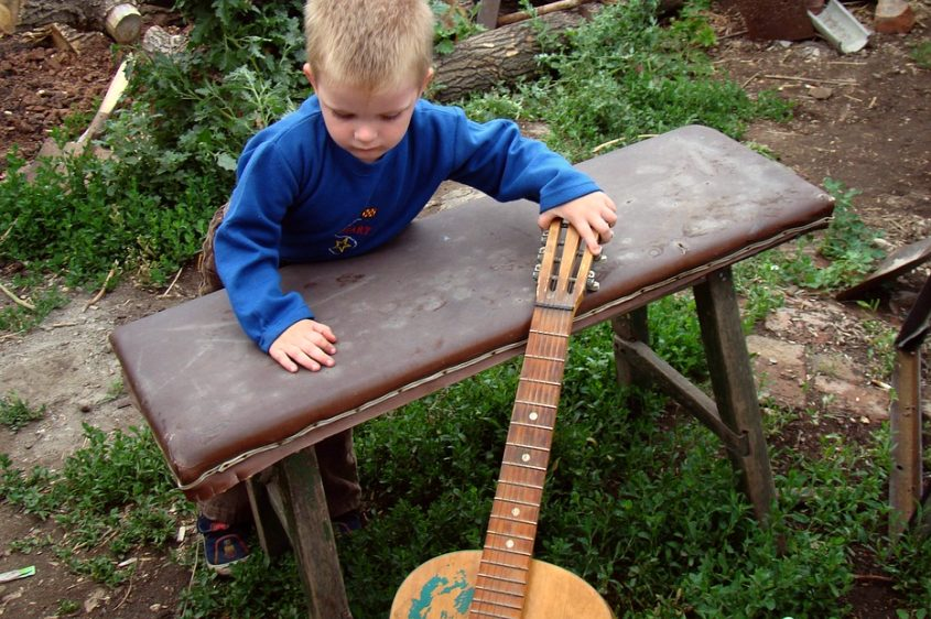 Little boy playing with a guitar in the back yard