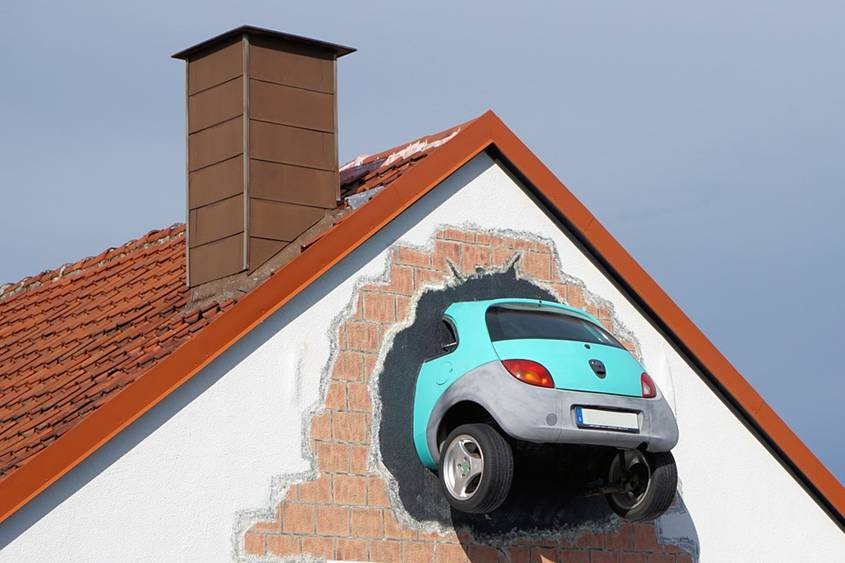 Back of a small car sticking out of the side of a house