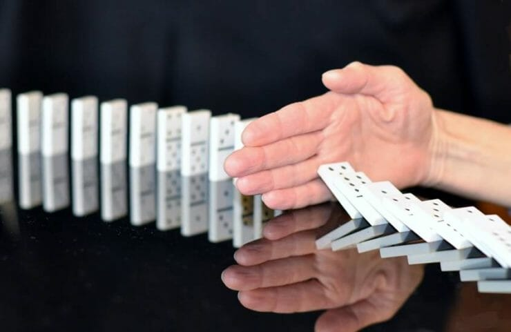 A row of dominos with a hand in the middle stopping them from continuing to fall