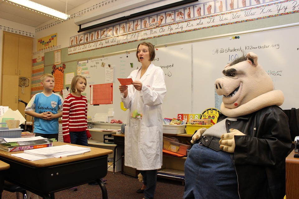 Teacher in a white coat and a pig sculpture with 2 children in a classroom