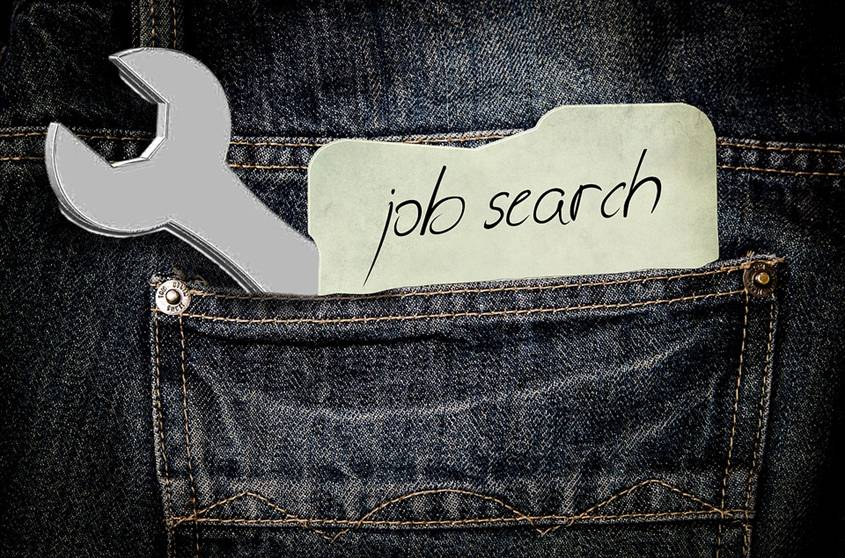 "Wrench and a note saying ""job search"" in the back pocket of jeans"