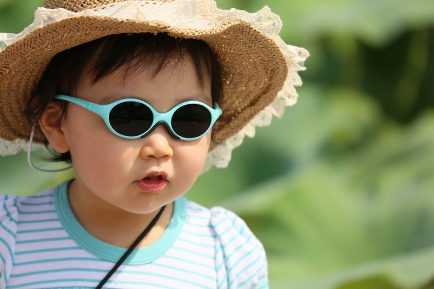 Toddler with sunglasses and a straw hat