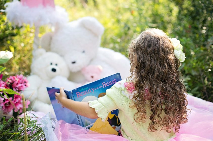 Girl reading a book to teddy bears