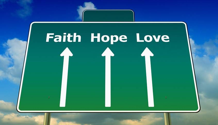 Road sign with arrows to faith, hope and love