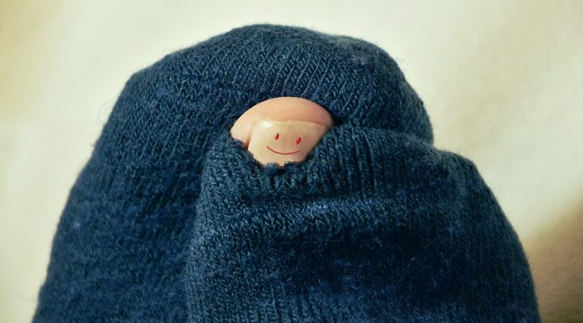 Toe poking through hole in socks with a smile on it