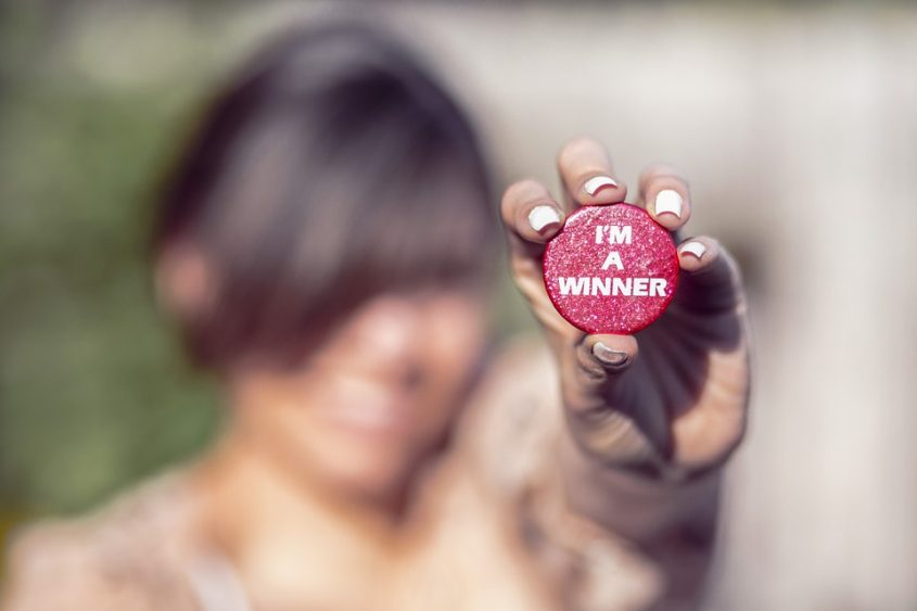 Woman holding up a button that says I'm a winner