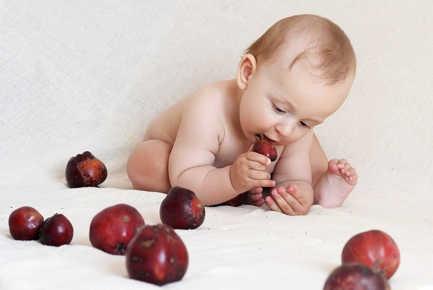 Baby tasting an apple