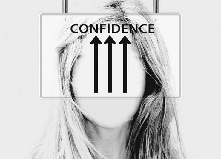 Faceless woman with a sign showing arrows pointing at the word CONFIDENCE