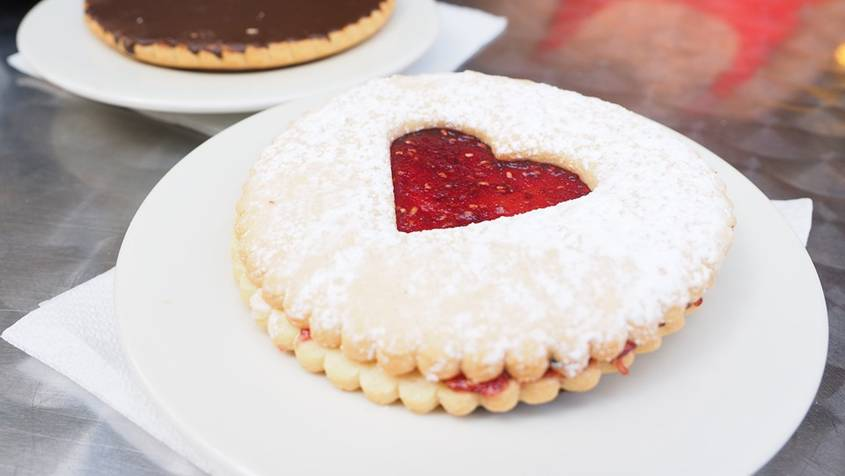 Cookie with a heart-shaped hole showing jam