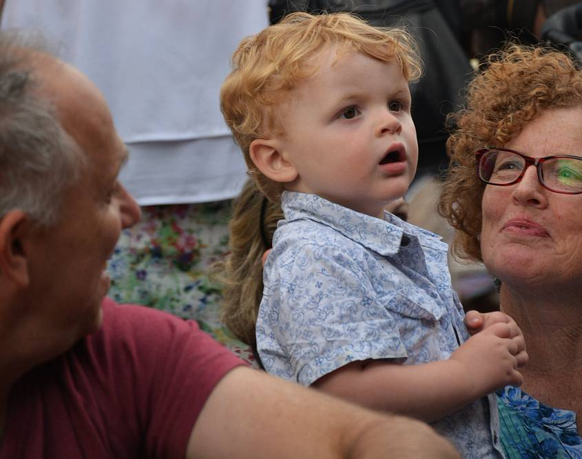 Toddler boy amazed by street performance