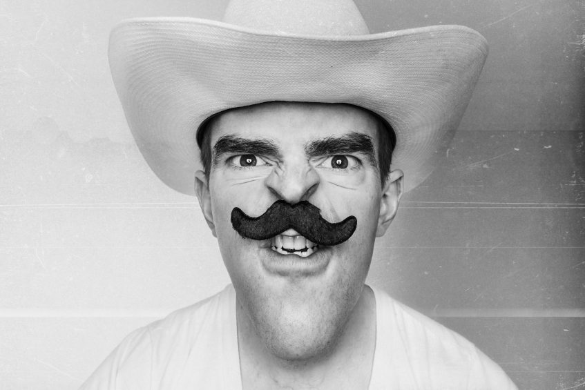 Man with moustache and cowboy hat looking angry